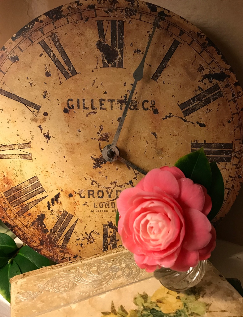 Vintage clock face and pink camellia in an old crystal salt shaker placed on a book called Bitter Sweet by J.G. Holland; written in 1858.